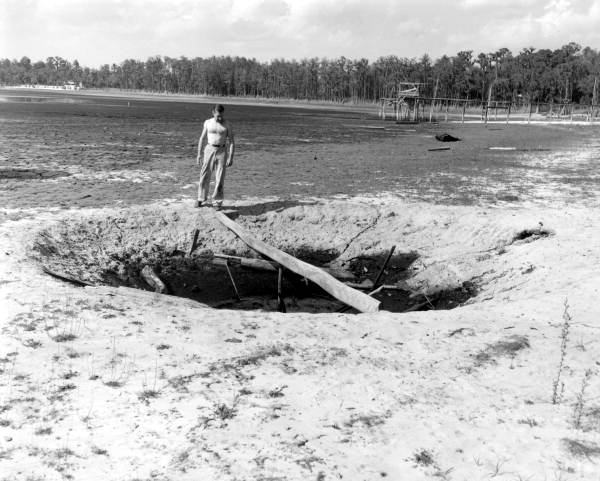 PHOTO: State Archives of Florida /George Grose standing at sinkhole by dried up Lake Bradford Leon County, Florida by Kerce, Red 1955