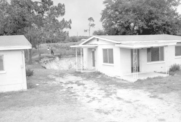 PHOTO: State Archives of Florida /house with sinkhole behind it by Reves, William D. 1963
